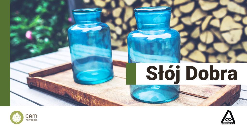 Dwa niebieskie, szklane słoje bez przykrywki stoją na drewnianej tacy. Po lewej stronie u dołu na białym tle napis: Słój dobra.
