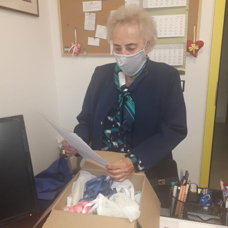 Seniorka w maseczce z pudełkiem woreczkami.