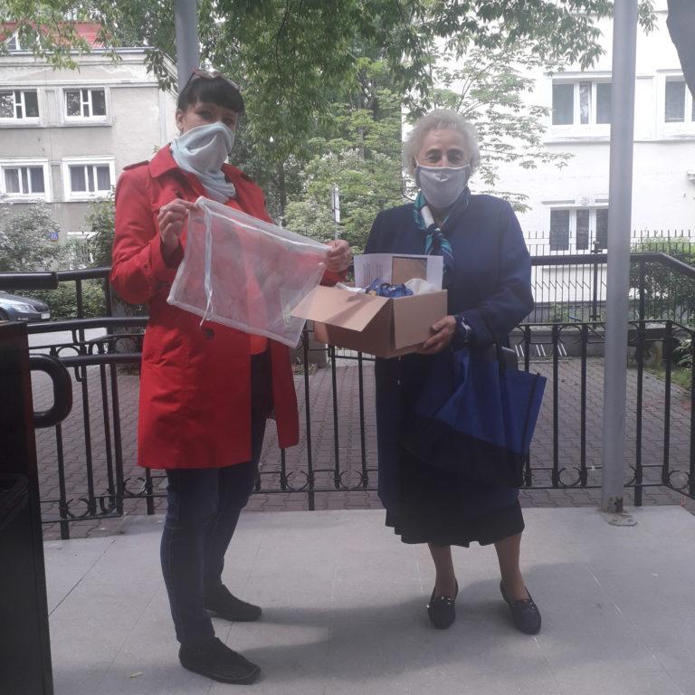 Seniorka przekazuje pudełko z uszytymi przez siebie woreczkami praconiczce CAM.