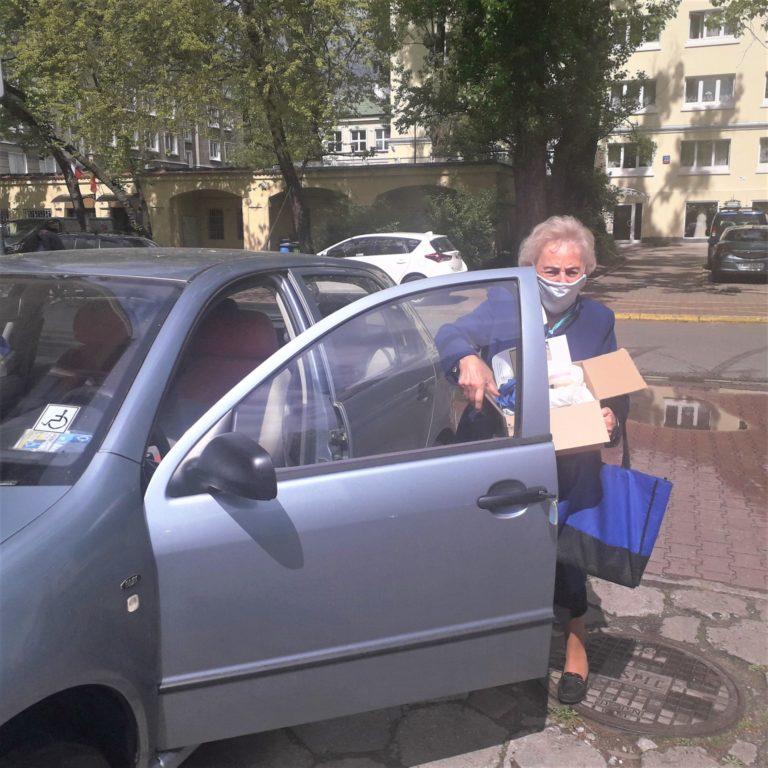 Seniorka wysiada z samochodu z pudełkiem z woreczkami.