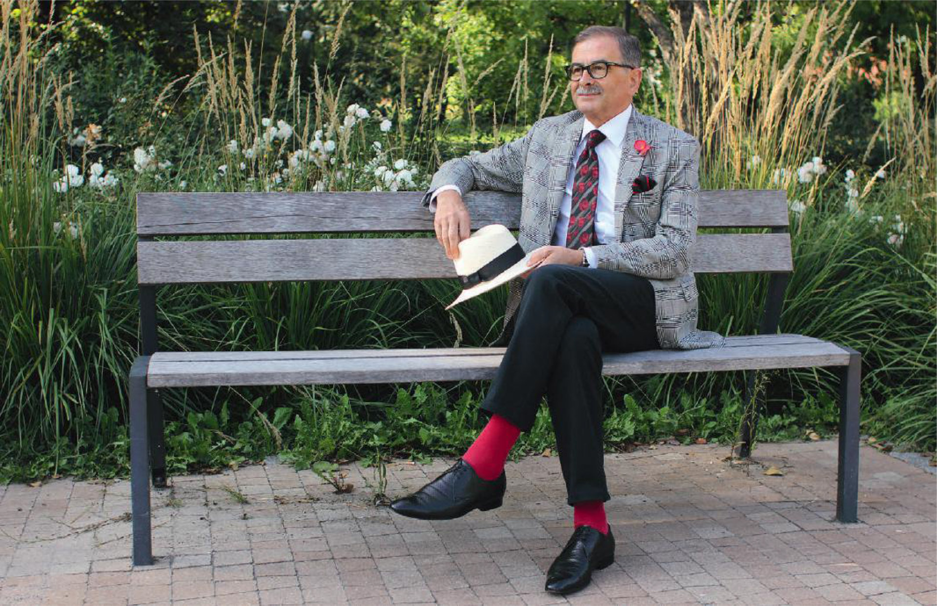 Starszy mężczyzna bardzo elegancko ubrany w garnitur i krawat, siedzi na ławce w parku. W ręku trzyma biały kapelusz.