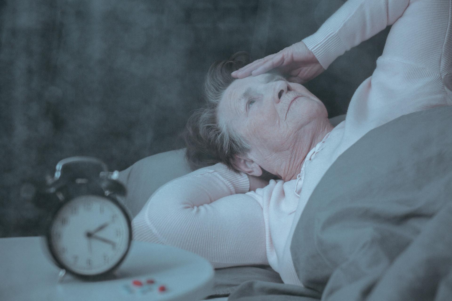 W lewej części grafiki widać starszą kobietę leżącą w łóżku, dotyka ręką głowy. Z lewej strony widać budzik.