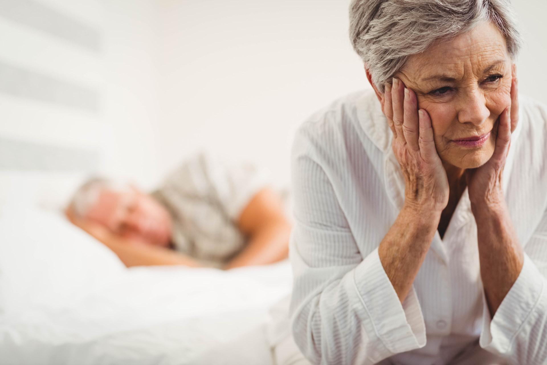 Na pierwszym planie starsza kobieta siedzi na łóżku, twarsz podpiera obydwoma rękami. Na drugim planie za nią śpi mężczyzna.