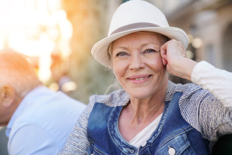 Starsza kobieta, uśmiechnięta, podpiera sobie ręką głowę, na której ma biały kapelusz.