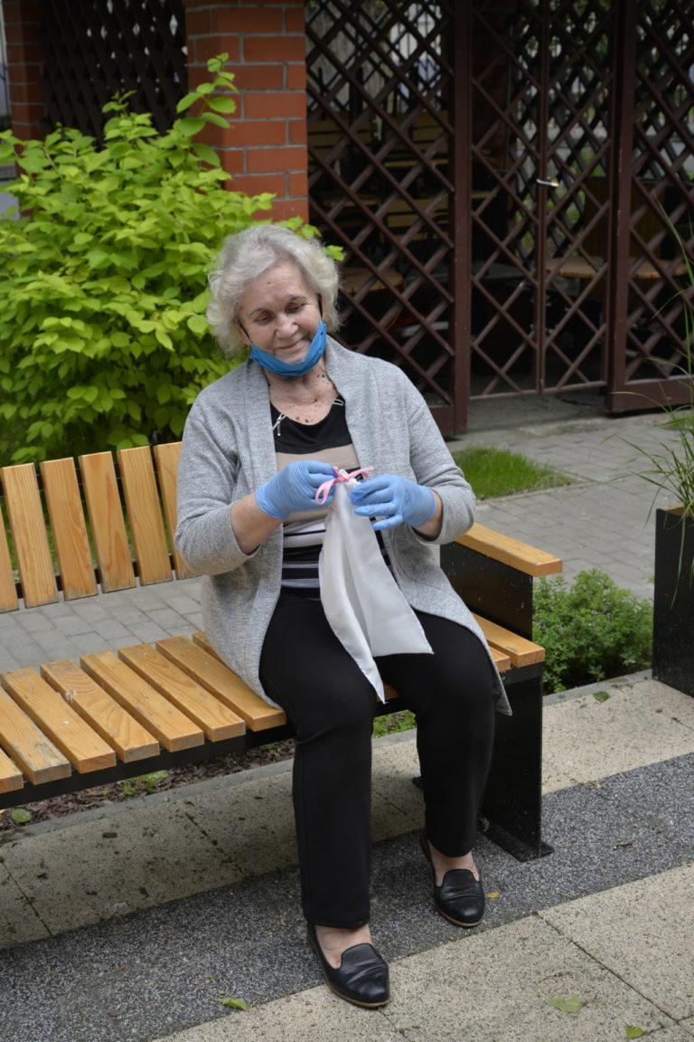 Seniorka, siedząca na ławce trzyma w ręku woreczek.