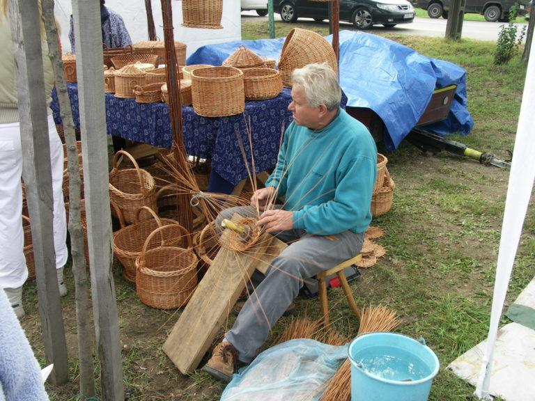 Mężczyzna wyplata wiklinowe kosz. Wokł niego stoi wiele gotowych koszy i pojemników wiklinowych.