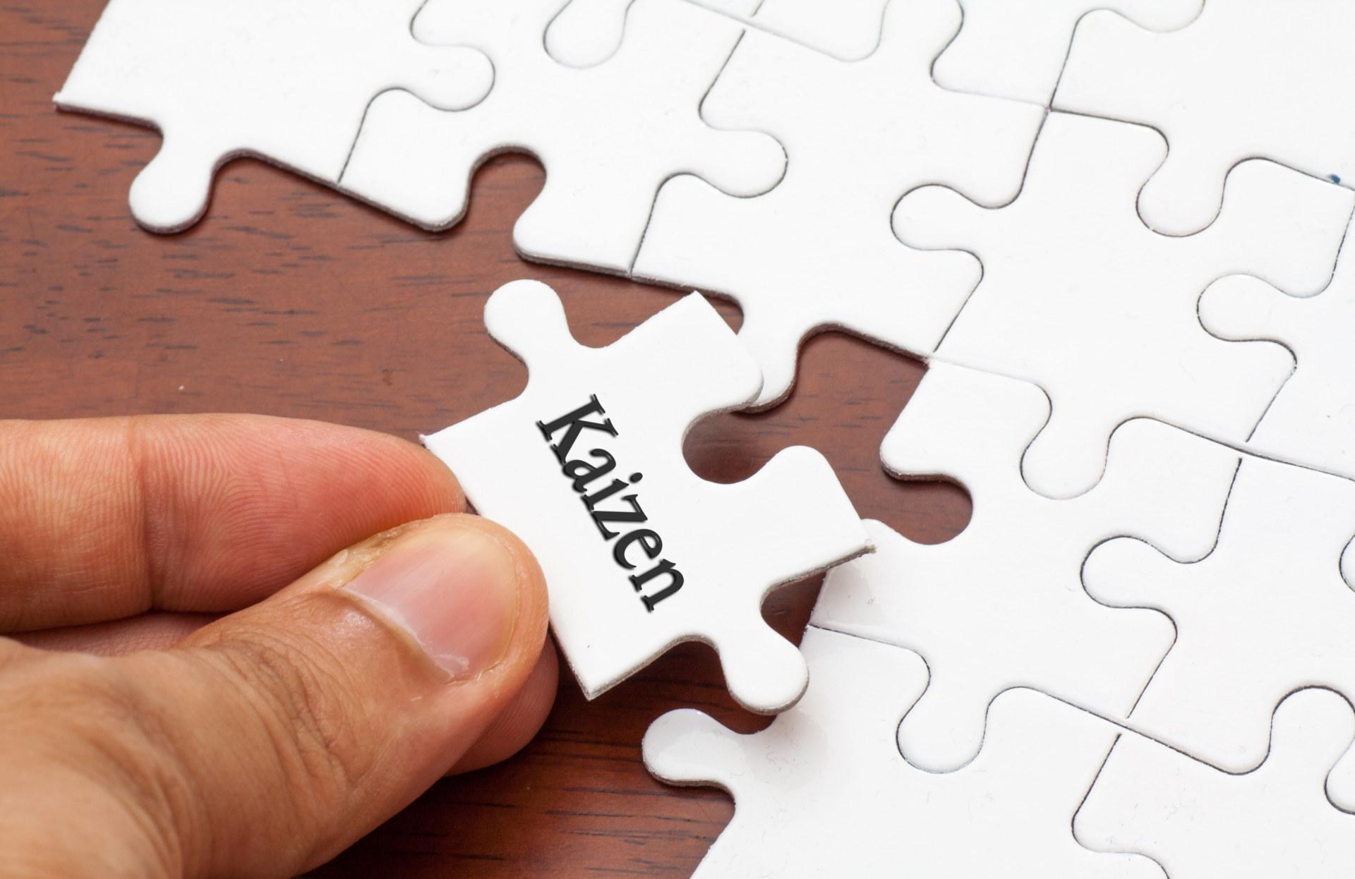 Białe puzzle ułożone na brązowym stole. Jeden z puzzli z napisem Kaizen trzymany w palcach.