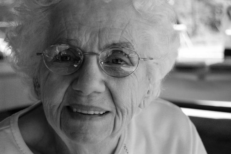 Czarno-biały portret seniorki w okularach.