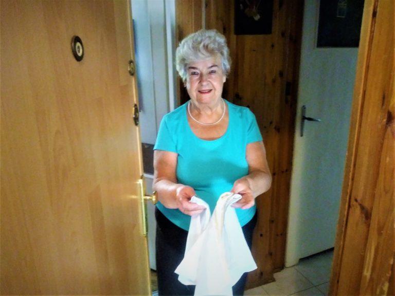 Seniorka w niebieskiej bluzce trzyma w ręku uszyte przez siebie woreczki.