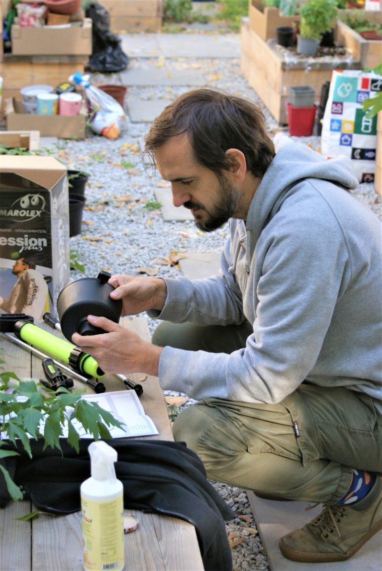 Mężczyzna skręca opryskiwacz do roślin.