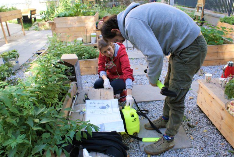 Kobieta i mężczyzna uruchamiają opryskiwacz do roślin.