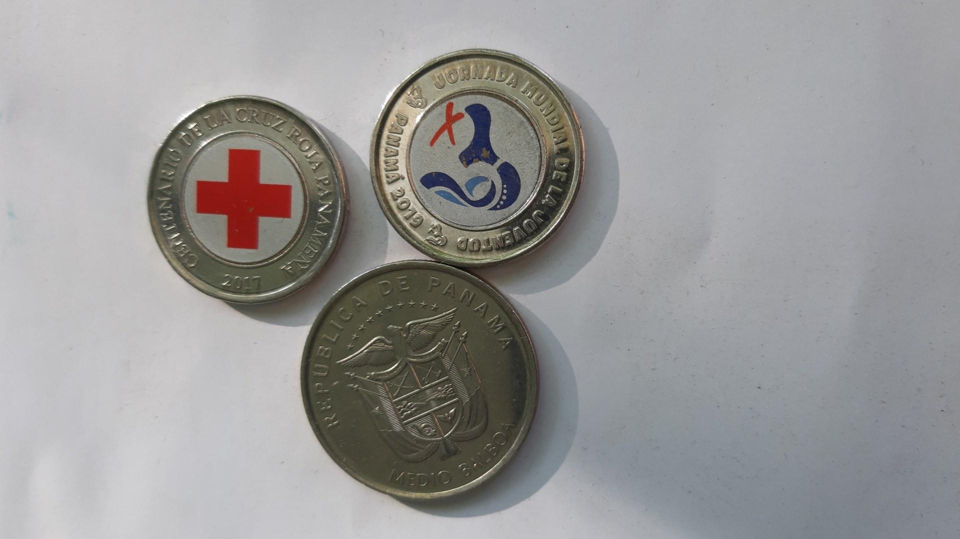 Trzy monety z różnycmi emblematami i kolorami.