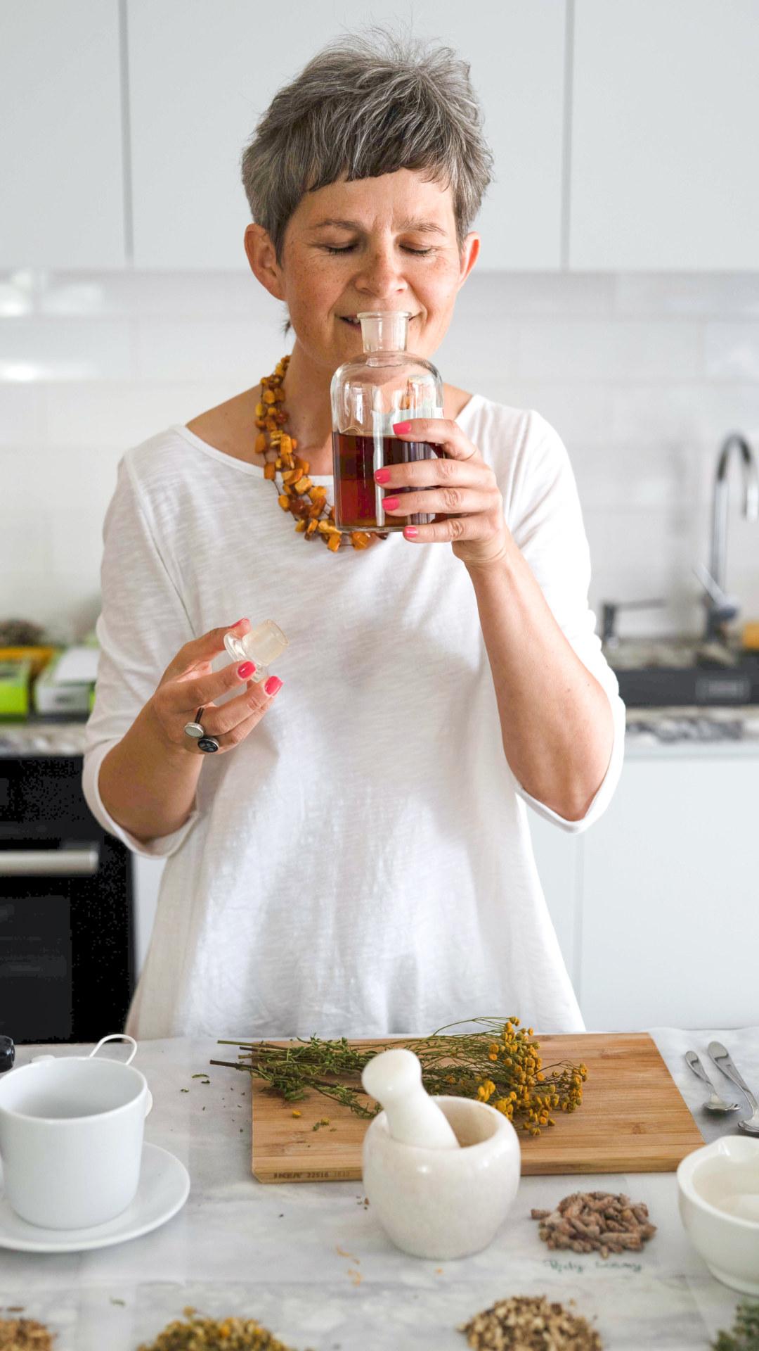 Kobieta wącha napar w butelce.