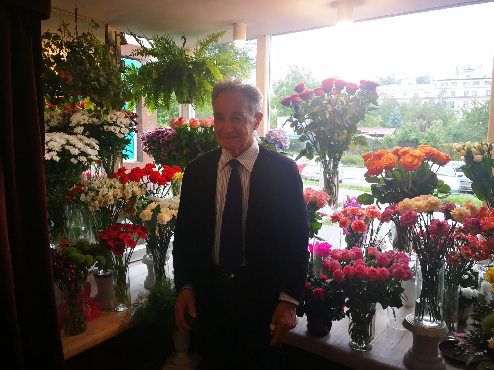Mężczyzna stoi wśród kwiatów w kwiaciarni.