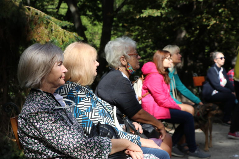 Uczestnicy w parku siedzą na ławeczkach.