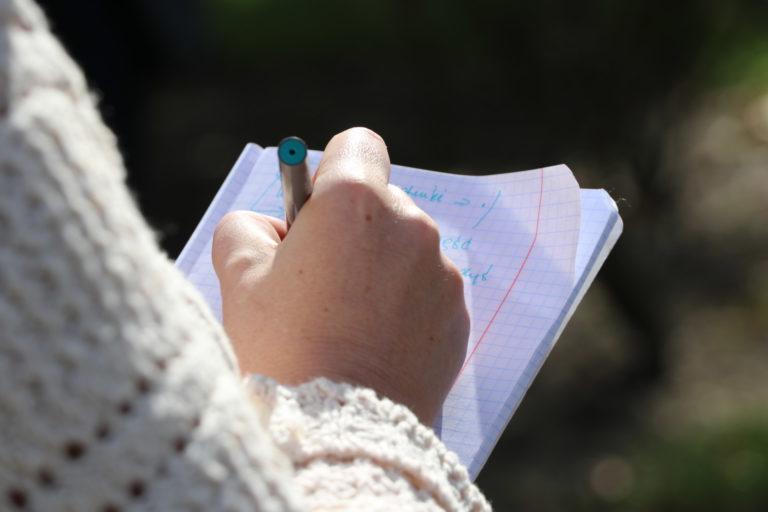 Ręka robiąca notatki w zeszycie.