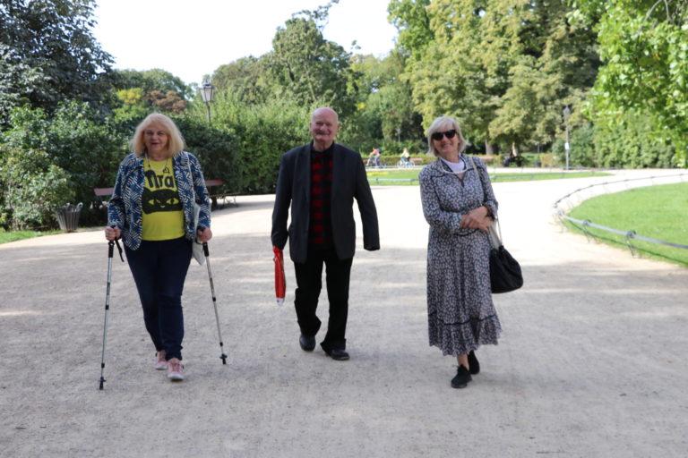 Seniorzy spacerujący alejką.