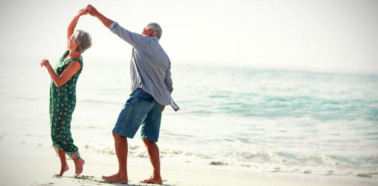 Para seniorów tańcząca nad morzem.