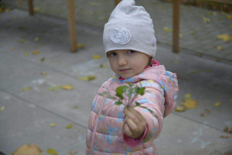Dziewczynka trzyma w ręku liście.
