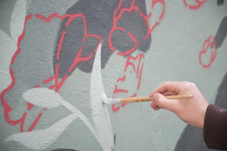 Elementy muralu, widać rękę z pędzlem