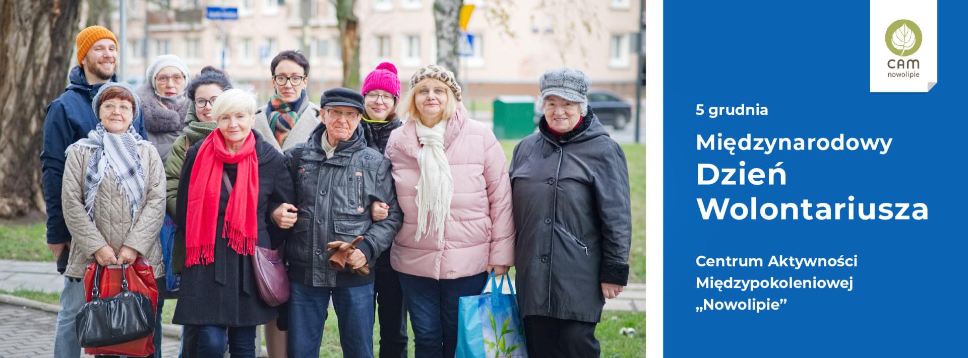 Grupa starszych i młodszych osób stoi przed kamerą.