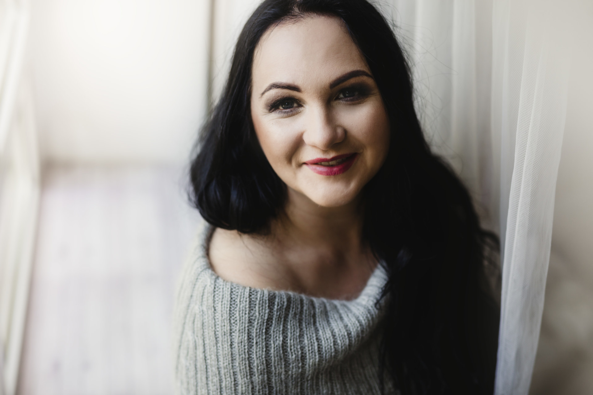 Kobieta z czarnymi włosami uśmiecha się.