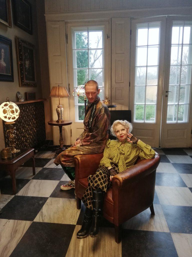 Kobieta na fotelu, na jego oparciu siedzi mężczyzna.