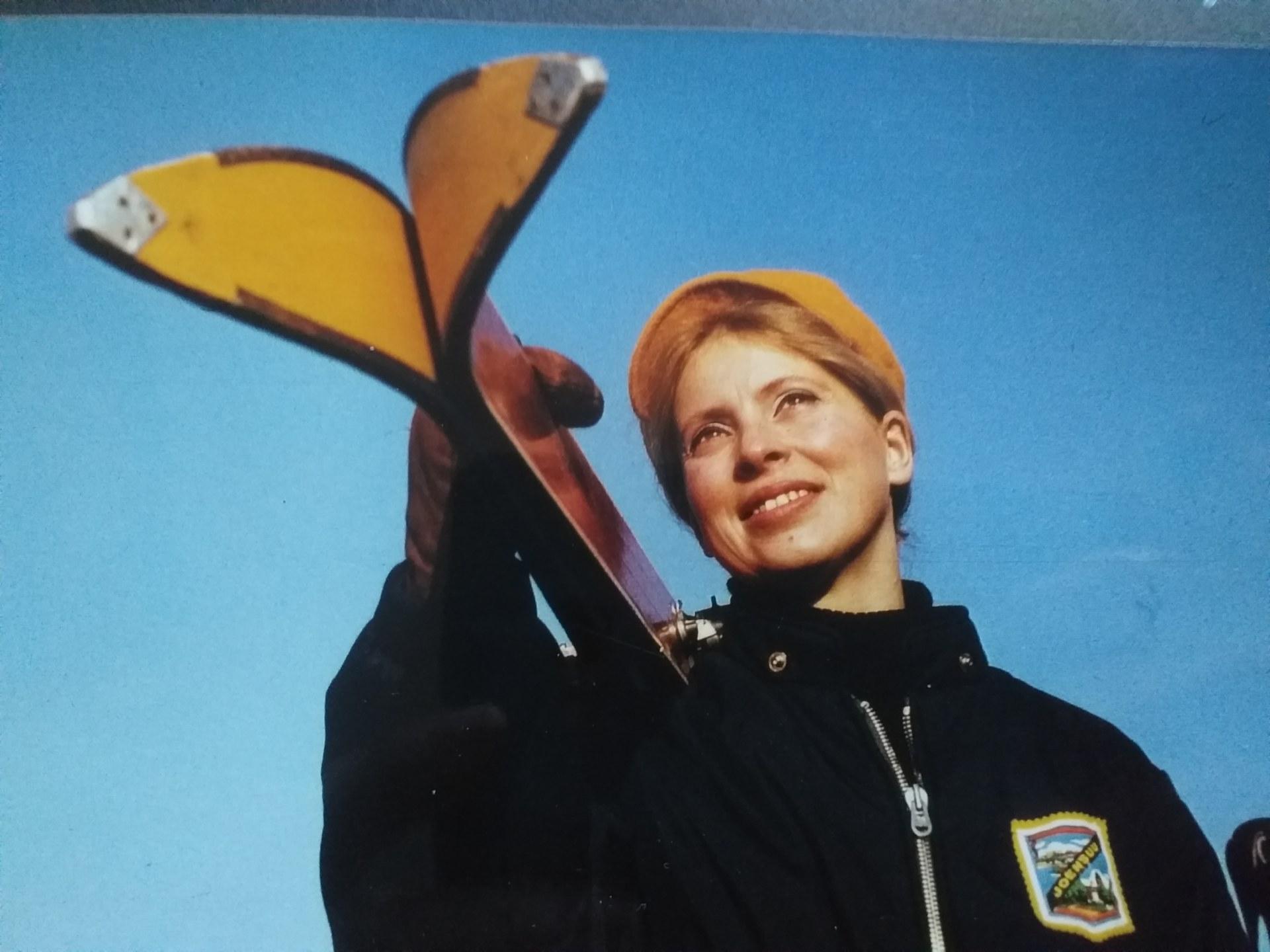 Kobieta w stroju narciarskim trzyma na ramieniu narty.