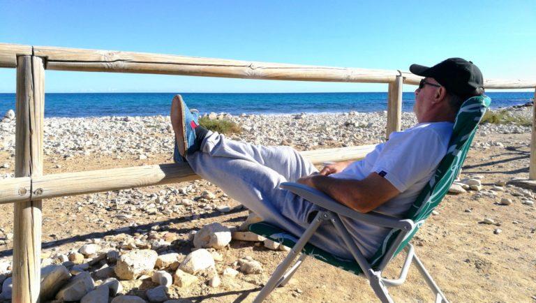 Mężczyzna na rozkładanym fotelu patrzy na morze.