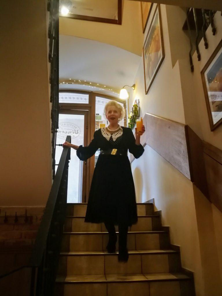 Seniorka w sukience schodzi po schodach.