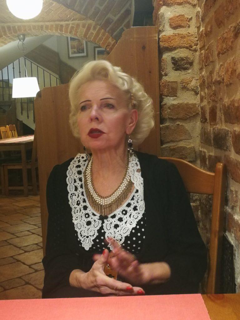 Piękna seniorka siedzi przy stoliku w kawiarni.