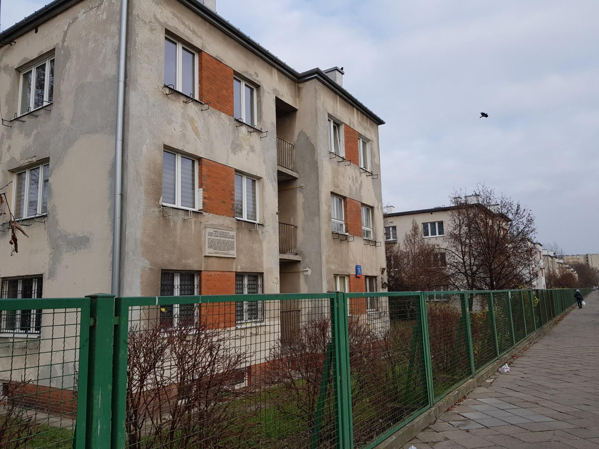 Dwupiętrowy budynek mieszkalny, zdjęcie zrobione z chodnika.