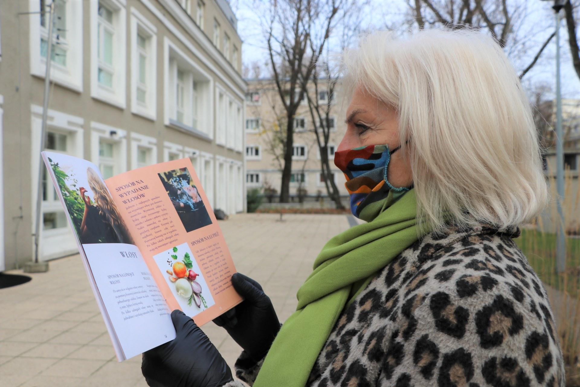 Seniorka stoi bokiem na twarzy ma maseczkę. w rękach trzyma broszurkę.