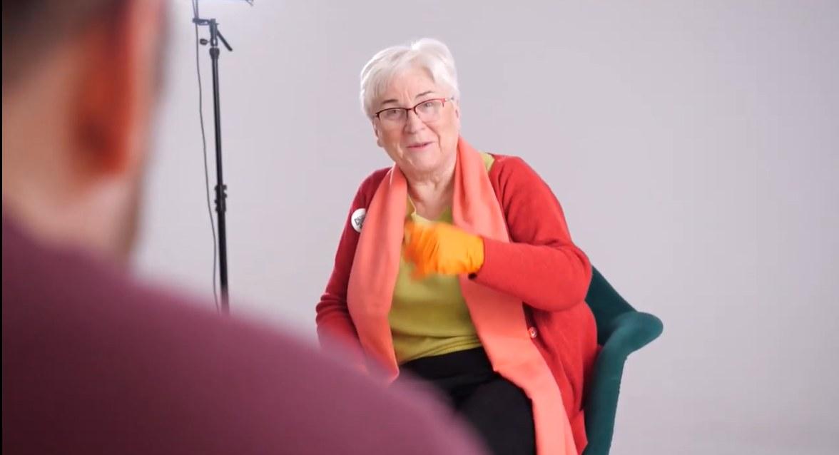 Seniorka przed nagraniem. Siedzi na krześle. Ubrana jest w czerwoną bluzkę i różowy szal. Po lewej stronie widać ramię operatora i stojak mikrofonu.