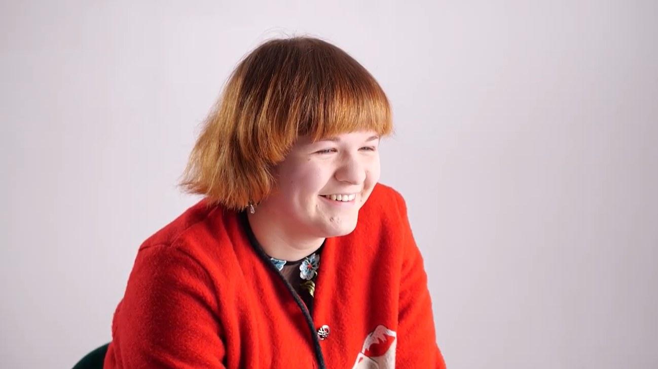 Młoda dziewczyna w czerwonej bluzce uśmiecha się.