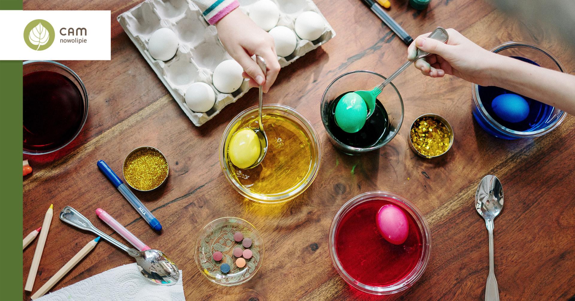 W szklankach w kolorowej wodzie barwią się jajka. Wokół rozrzucone na stole materiały dekoracyjne.